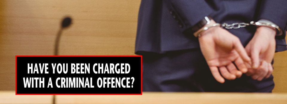 Man in court wearing handcuffs - Have You Been Charged with a Criminal Offence?